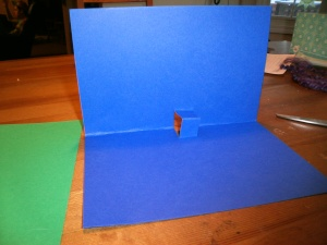 Unfold the cardstock so the two halves sit at a right angle to each other and poke the little tab you made forward to it sits up. This will be what allows your walrus to pop-up.